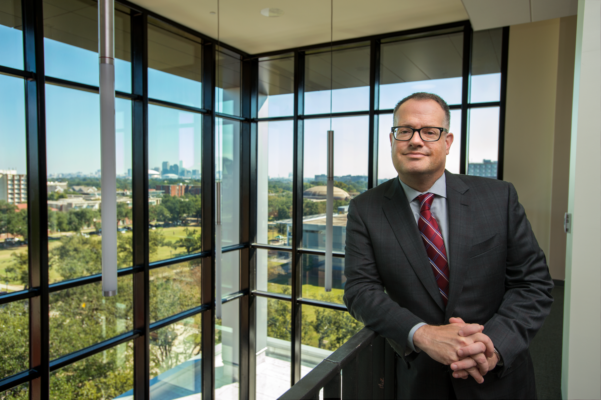 Portrait of Dean Banush standing on the balcony overlooking the 5th floor atrium and view of New Orleans. He is wearing glasses