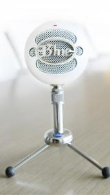 White Snowball brand microphone perches like a large snowball on top of a small chrome microphone stand.