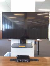 Head on view. A large screen hung on a white column. A half circle table below the screen includes a headphone amp.